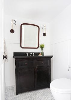 This+powder+room+features+white+hexagon+tile+flooring+and+a+single+black+vanity.