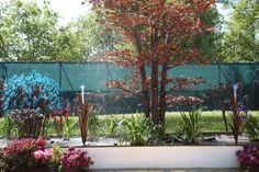 Quist Ltd show us that mixing greens with copper tree water sculptures works. #gardening #gardendesign #RHSChelsea