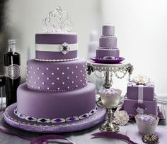 Three tier cake made with lavender fondue. A silver Tiera serves as the topper, a white ribbon comes around the top layer closed with an amethyst broach.  Different jewels are used to separate each layer. The middle tier is encrusted with many white beads. A mini version uses pearls as the divider.