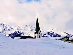 Kirchturm im Pillerseetal schaut aus dem Schneehügel heraus