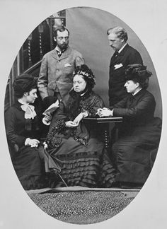 Photograph of Queen Victoria sitting with Princess Louise, Marchioness of Lorne reading a book; Prince Leopold and the Marquess of Lorne standing behind the Queen and Princesses and Princess Beatrice who has her arms resting on a table Queen Victoria Children, Queen Victoria Family, Queen Victoria Prince Albert, Victoria And Albert, Princess Louise, Princess Beatrice, Windsor, British History, Asian History
