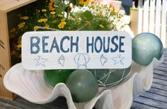 """This is a very rustic beach/cottage style """"Beach House"""" sign with white & blue coastal color. Hand carved and hand painted. Measures 14 inches long."""