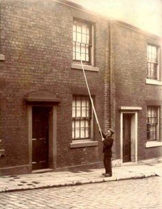"""A """"knocker-up"""" waking up clients (20th century)."""