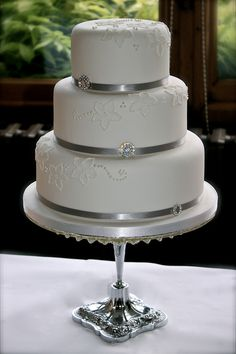 Small,Simple  Elegant but with buttercream - no fondant....red ribbon w/ gems? or black ribbon with red gems? Like the idea of putting small cake on pedestal.