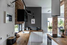 Aranżację otwartej kuchni oparto na nawiązującej do pozostałej części dziennej domu palecie barw w szarości i bieli....