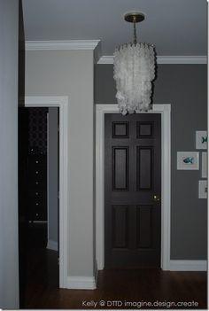 Black doors, white trim, and double grey walls in the hall way Black Interior Doors, Interior Paint, Grey Walls White Trim, Gray Walls, Black Trim, Wall Colors, House Colors, Hallway Colours, Dark Doors