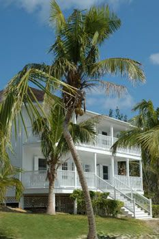 Oh goodness!!! Wrap around porches! White house, Coconut trees... I bet there is a view of the sea!!!