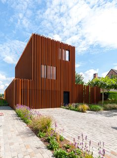Strips of pre-rusted Corten steel run in vertical columns around this Belgian house.