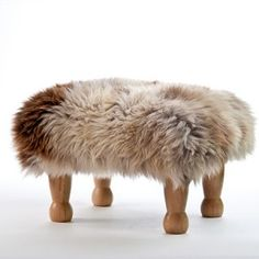 Angharad in Rare Breed.  A luxury sheepskin footstool with sturdy natural coloured legs and a removable real British sheepskin cover handmade in beautiful North Wales. The Angharad is the ideal 'level' foot stool.