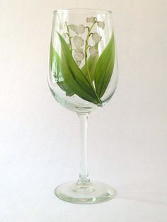 Sweet white floral bells and bright green leaves hand-painted encircling a quality 18.5 ounce wine glass. Sealed and heat-cured for added durability. Top-rack