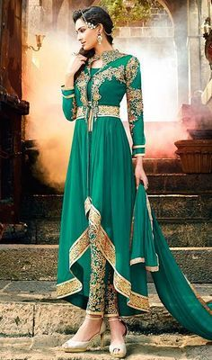 Imprint a lasting impression on everyone you meet dressed in this pant style dress in bottle green color embroidered silk. Beautified with lace, patch, resham and stones work. #pantstyledress #greensuit #designersuitcollection