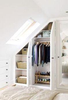 Dressing sous pente avec deux portes en blanc et fenêtre sur le côté. Paniers beiges tressés, vestes, chaussures, talons et sacs rangés.
