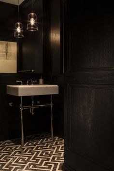 A small space can be the perfect choice for dramatic design decisions, as seen in this black powder room. The graphic patterned black and white tile flooring gets to steal the scene.