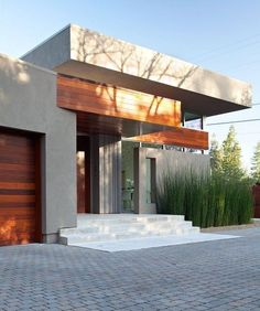 Timber garage door, render and cobblestones | Home in Menlo Park, California designed by Dumican Mosey Architects - photo by Mariko Reed