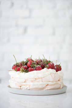 ... pavlova topped with fresh strawberries and whipped cream ...