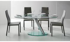 Très belle table ronde avec un plateau et une rallonge en verre et une mécanique en acier pour assurer une solidité.