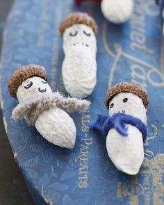 so fun and easy you can do it with the kids!  1. Paint your peanuts white and set aside to dry. 2. Hot glue the acorn topper on as a hat. 3. Tie a ribbon scarf around the neck. 4. Draw on a face with a sharpie. Make different expressions on each peanut! 5. If you want to hang them just hot glue a thin string on top of the hat.