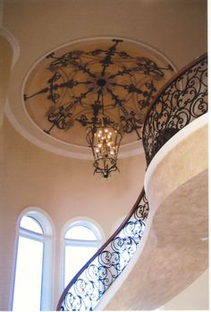 Elegant stairway with stunning mural on the ceiling.
