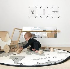 What a lovely kid's play room! OYOY The World Rug and Ooh Noo Toy Pram are all available online.