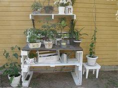 Pflanztisch aus weiß gestrichenen paletten un Holzplatte