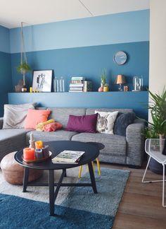 woonkamer - Kleur is erg belangrijk voor ons. We hebben blauw als basiskleur gekozen en hebben vervolgens met accessoires vele verschillende kleuren toegevoegd. De verhoging achter de bank is zelfgemaakt. De accessoires zijn door de jaren heen verzameld van komen onder andere bij Loods5, Wehkamp en Ikea vandaan.