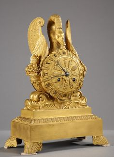 Early 19th century French Clock in ormolu with a swan and cornucopia Original and unique clock in gilded bronze, Charles X period, representing a swan spreading out behind a movement with Roman numerals and resting on dolphins. The dial in bronze, chiseled with various patterns of shells for each hour, is flanked by cornucopias from which flow out fruits. The rectangular base rests on four legs in the shape of shells imitating stylized waves.