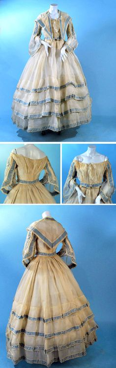 Summer organdy 3-piece promenade gown ca. 1860s. Off-the-shoulder bodice with ruching at front & back at waist. Open pagoda sleeves, with blue ribbon accents throughout. Skirt with many layers of blue-trimmed ruffles. Bodice has cotton inner liner with hook & eye closure. Carolyn Forbes Textiles/ebay