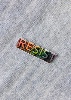 "This cute enamel pin has the quote ""Resist"" in rainbow colors. It's the perfect way to dress up your denim jacket with lgbtq pride."
