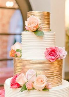 gold and ivory white buttercream four tier wedding cake with bright fresh rose flowers