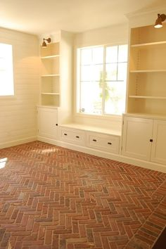 Horizontal planked walls, built-in storage with library-style lights & window seat, worn brick flooring in herringbone pattern
