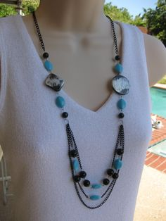 Long black and turquoise beaded necklace on black multi strand chains, with large black beads with silver brush strokes. Necklace is 34 inches