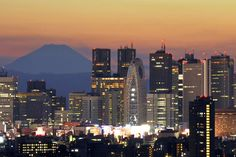 Mount Fuji rises up behind the skyscraper skyline as the sun sets over Tokyo.