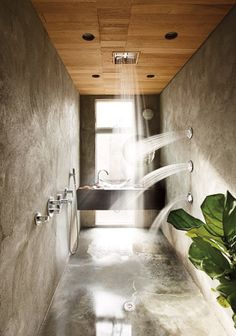 Stucco shower with numerous showerheads and wooden ceiling designed by Hank Mitchell.