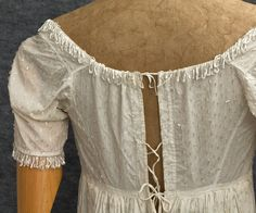 """French beaded cotton evening dress, c.1805 Made from white cotton muslin, the peerless Directoire dress is totally covered with opaque white Bohemian glass bugle beads. The neckline and sleeves are bordered with loops of beads. Such a simple high style gown could have been worn by a wealthy, aristocratic Russian girl to her first grand ball.  It measures: 32"""" bust, 27"""" empire waist, 10"""" from the shoulder to the empire waist, and 55"""" from the shoulder to the hem (slightly longer in back)."""