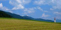 Il campanile della Parrocchiale di Villabassa spunta dietro i campi della Val Pusteria.
