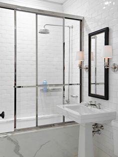 Contemporary bathroom features black mirror flanked by polished nickel sconces over pedestal sink leaning against wall clad in floor to ceiling subway tile backsplash which extends to the shower/tub combo accented with white marble surround, rain shower head with exposed plumbing and polished chrome and glass sliding shower door.