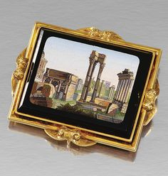 GOLD AND MICRO MOSAIC BROOCH, MID 19TH CENTURY.  The rectangular black glass tablet inset to the centre with a scene of the Roman Forum depicted in multi-coloured tesserae, to a frame decorated with engraved scroll motifs, accompanied by a fitted case by Watherston & Brogden, Goldsmiths, Manufactory, 16. Henrietta St. Covent Garden, London.