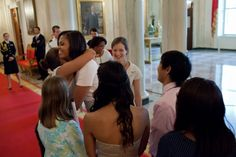 First Lady @Michelle Obama greets White House mentees in the Cross Hall of the White House before an event celebrating their graduation