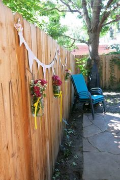 Backyard bridal shower - mason jars hanging from fence with flowers