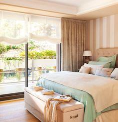 Dormitorio en tonos beige y verde agua con pared del cabecero en papel pintado a rayas