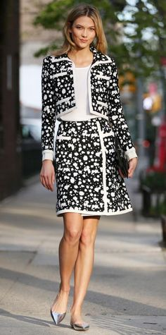 Karlie Kloss wearing a black-and-white paint-splattered suit set, with a white top, black clutch and mirrored silver flats.