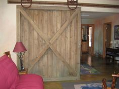 Old barn door hardware came in handy for this room separator... the wood was actually new but faux painted to have weathered look