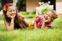Cute two sisters laughing and having fun in the grass