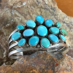 This beautiful Sterling Silver Cuff Bracelet features 15 stones of Carico Lake Turquoise, exhibiting both the green and blue hues characteristic of this stone. Crafted by Native American artists. Colo