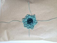 For this project you will need two different size crocheted doilies, 1m long cord or thin ribbon, a 4-hole button and 1 ready wrapped gift.           To make a crocheted flower decoration: 1. pull the cord/ribbon through the crocheted doilies, button hole and back, 2. pull the cord/ribbon through the doilies …