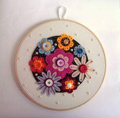 Quadro de bastidor em madeira de diâmetro de 20 cm, fundo em tecido, mandala em feltro com flores de feltro delicadamente bordadas, miolo de botão e com aplicação de meia pérola em todo o quadro.