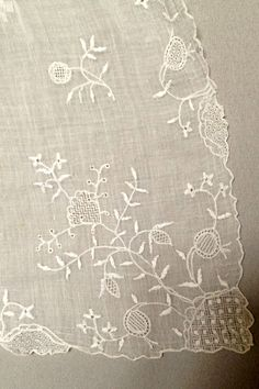Detail, long apron, 1770-1790. Fine white muslin tambour embroidered throughout with rows of white cotton single and double flower sprigs, with twelve different designs, the lower corners with stylsied flowerhead surrounded by tendrils and leaves emerging from a drawnthreadwork rocky mound, the borders with gently scalloping with curving flower stems and cartouche infills, gathered onto a silk ribbon.