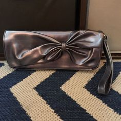 Silver Bow Clutch Cute and roomy silver bow clutch! Perfect for prom! Never used it, three pockets, and wrist strap, with big bow in front. Holds iPhone 6s+ with lots of room to spare for the girls necessities. 10 inches by 4.5 inches Bags Clutches & Wristlets