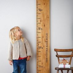 The \'Kids Rule\' wooden ruler height chart is a handmade, personalized wooden growth chart, designed as a giant vintage wooden ruler by Lovestruck Interiors.  These make original Christmas gifts, christening gifts, first birthday presents and new baby presents for boys and girls.  By personalizing them with a family name (rather than the child\'s), they can still be used if further new additions arrive later on.