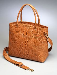 The Town Tote concealed-carry purse is American cowhide, with debossed croc pattern.  Ambidextrousa access to gun compartment!